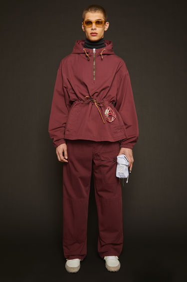 Acne Studios burgundy trousers are made from cotton that's garment-dyed to create light fading at the seams. They're cut in a straight shape that drapes loosely over the leg and finished with an elasticated drawstring waistband and a utilitarian flap pocket.