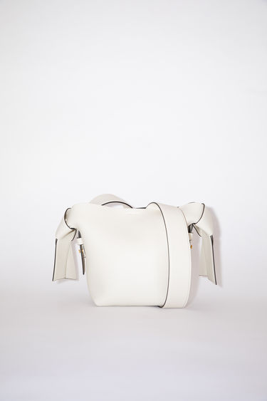 Acne Studios white/black small bag features twisted knots inspired by traditional Japanese obi sashes. It has a debossed logo and snap button closure, which opens to reveal a zipper compartment for storing small essentials.