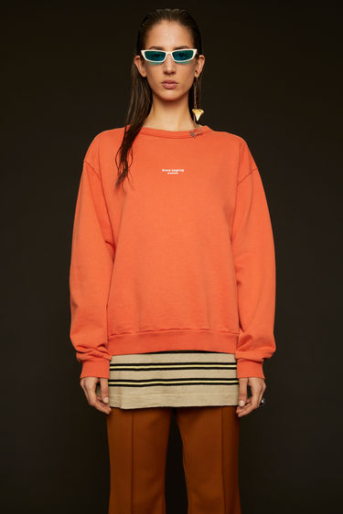 Acne Studios poppy red sweatshirt is made from cotton jersey that's been garment dyed for a soft, washed-out finish and features a reversed logo purposely printed imprecisely across the front.