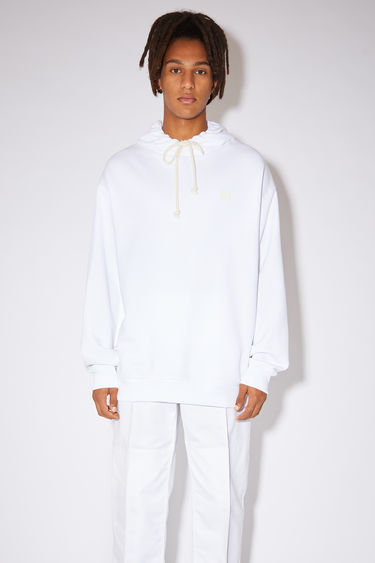 Acne Studios optic white hooded sweatshirt is crafted from midweight loopback fleece to an oversized fit and finished with a tonal face patch on the chest.