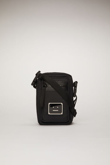 Acne Studios black pocket bag is made from technical ripstop with a detachable crossbody strap and an array of zip and mesh pockets, then accented with a polished metal logo plaque that depicts a face motif in black.