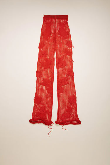 Acne Studios red trousers are crafted from a wide-gauge cotton-blend knit and patterned with an abstract flower motif. It's shaped to high-rise silhouette with skinny legs and finished with rolled edges.