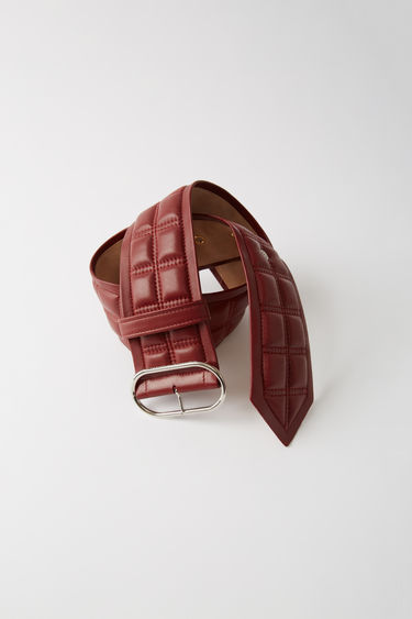 Acne Studios burgundy waist belt is crafted from quilted lamb leather and accented with a silver-tone oval buckle.