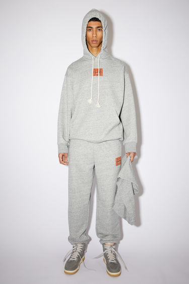 Acne Studios marble grey melange oversized hooded sweatshirt is made of a cotton blend with a basketball face print and ribbed details.