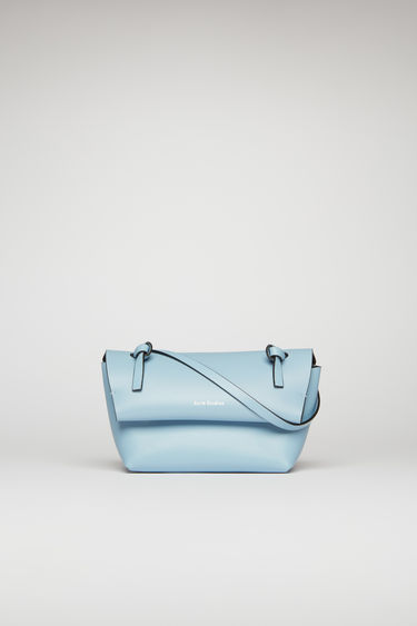 Acne Studios light blue/black mini purse is crafted from soft cow leather and detailed with an obi-inspired knot on each end of the crossbody strap.
