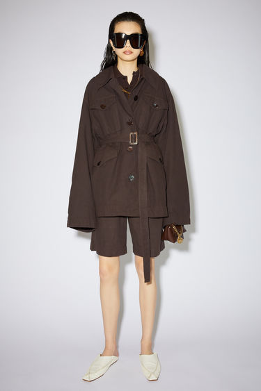 Acne Studios dark brown belted coat is made of cotton with a relaxed fit.