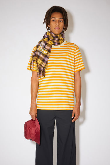 Acne Studios deep yellow striped t-shirt is made from organic cotton with a crew neck, relaxed fit, and a face logo patch.