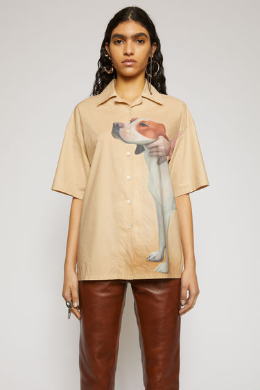 Acne Studios beige shirt is cut to a boxy silhouette with an open collar and short sleeves and features a prize dog print created by British artist Lydia Blakeley.