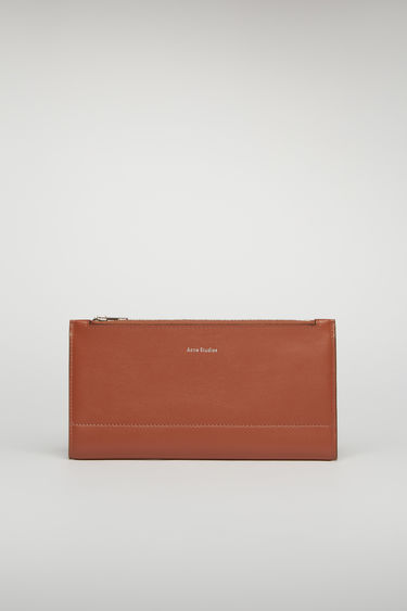 Acne Studios almond brown continental wallet features a smooth leather construction and it opens to reveal 12 card slots, a zipped pocket and two notes compartment.