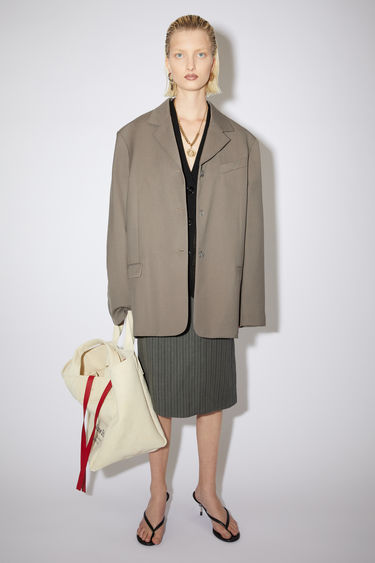 Acne Studios taupe grey single-breasted suit jacket is made of a wool blend with an oversized fit.