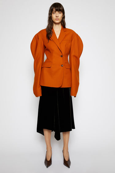 Acne Studios saffron orange suit jacket is crafted from wool with voluminous puff sleeves and features a wrap-over single-breasted fastening that cinch the waistline into a feminine silhouette.