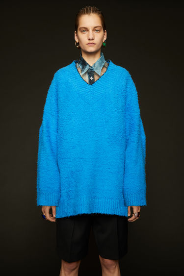 Acne Studios bright blue sweater is crafted from a cotton-blend that's been brushed to a teddy bear-like texture. It's shaped to an oversized fit and neatly finished with a ribbed v-neck with contrasting black edges.