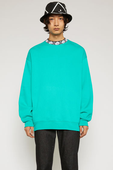 Acne Studios jade green sweatshirt is crafted from midweight brushed jersey to an oversized fit and features a ribbed mock neck inlaid with a face-jacquard design.