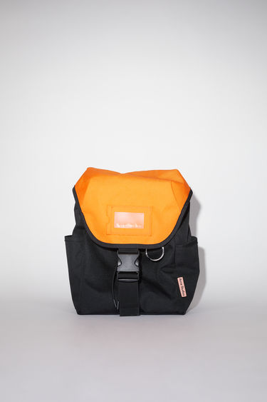 Acne Studios black/orange durable backpack has a clear vinyl ID pocket, two generous side pockets, adjustable straps, and an Acne Studios logo tab.