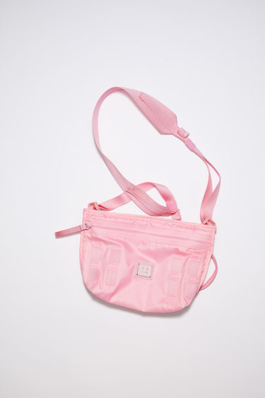 Acne Studios bright pink crossbody bag is made from technical ripstop and features a silver-tone metal logo plaque with a face motif in black. It has a front zipper pocket, mesh pocket, and an adjustable buckle strap.
