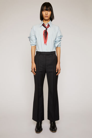 Acne Studios navy blue pinstripe trousers are crafted from wool and are cut to fit slim through the hips before falling into kick-flare legs.