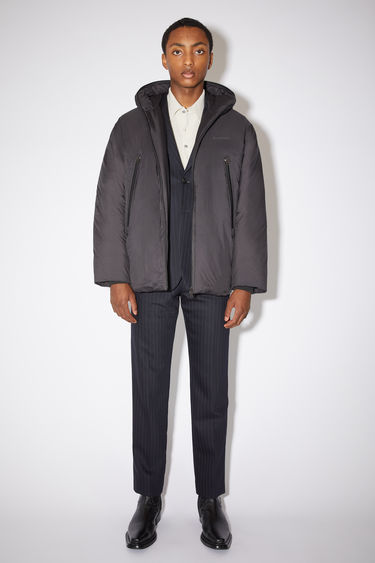 Acne Studios black hooded down jacket is made of nylon with a quilted interior and Acne Studios branding at the chest.
