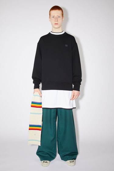 Acne Studios black crew neck sweatshirt is made of organic cotton with a face patch and ribbed details.