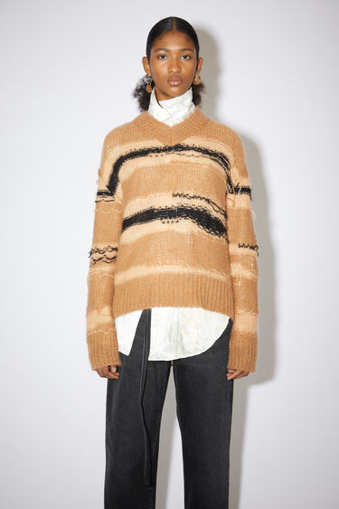 Acne Studios camel/black v-neck sweater has textured, irregular stripes and a short, relaxed fit.