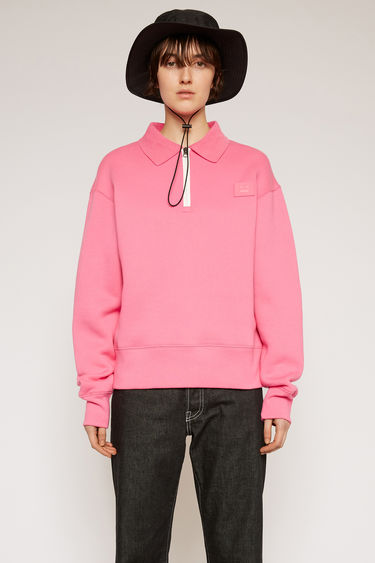 Acne Studios bubblegum pink is crafted from heavyweight fleece jersey to an oversized silhouette with a contrasting half-zip closure and point collar and accented with a tonal face-embroidered patch on the chest.