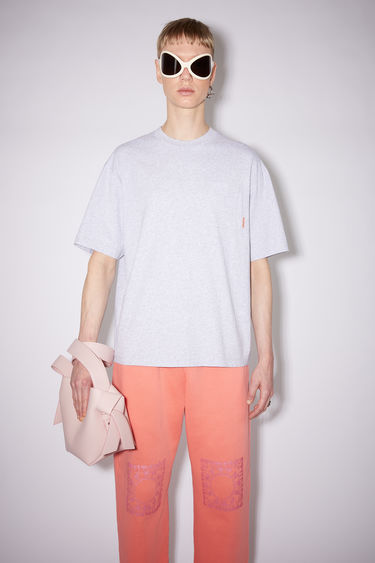 Acne Studios pale grey melange crew neck t-shirt is made of cotton, featuring a single chest pocket with an Acne Studios logo tab.