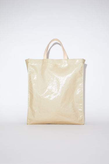 Acne Studios beige shiny tote bag features a small Acne Studios logo on the front and logo-debossed leather along the interior top edge.