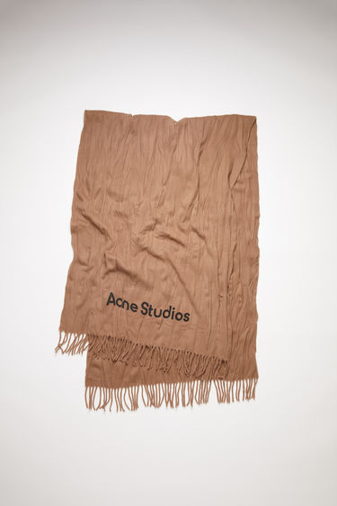 Acne Studios caramel brown scarf is crafted to a wide dimension from wool with crinkle effect and features a jacquard logo above the fringed edges.