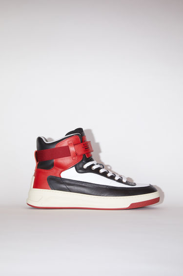Acne Studios black/red/white lace-up high top sneakers are made of calf leather with a face motif on the back sole.