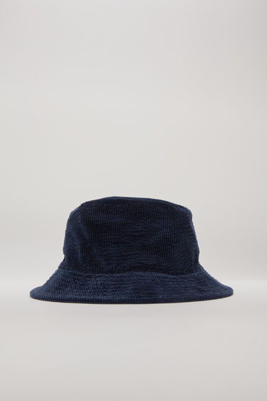 Acne Studios navy blue corduroy hat is shaped with a flat-topped crown and quilted brim and then accented with an embroidered logo on the side.