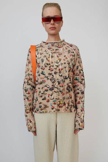 Acne Studios beige/multi cable-knit sweater is crafted from wool and patterned with a blurred crowd print.