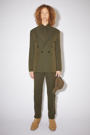 Acne Studios hunter green double-breasted suit jacket is made of a cotton blend with a classic fit.