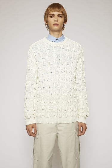 Acne Studios champagne beige sweater knitted from cotton blend to a cable pattern and completed with a ribbed crew neck, cuffs and hem.
