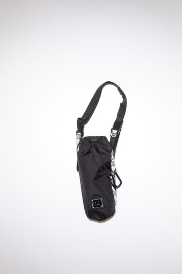 Acne Studios black bottle bag is made from technical ripstop, with a detachable crossbody strap featuring a face logo design. It has a drawstring closure and a dogclip.