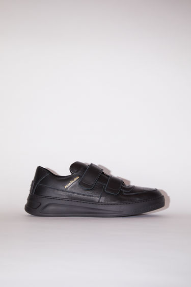 Acne Studios black/black velcro strap sneakers are made of calf leather with a round toe and a face motif on the back sole.