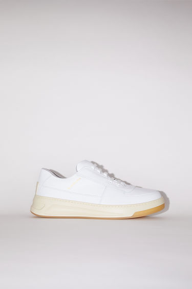 Acne Studios white/white sneakers take design cues from 80s tennis shoes. They're made of calf leather with a low top silhouette and embossed with a gold logo on the side.