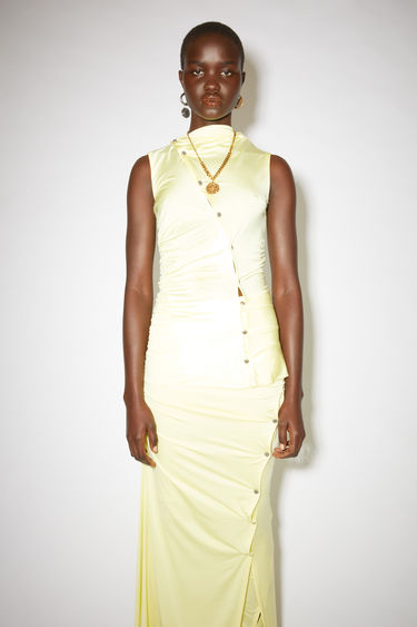 Acne Studios lemon yellow asymmetric sleeveless shirt features ornate metal button closures across the front and back.