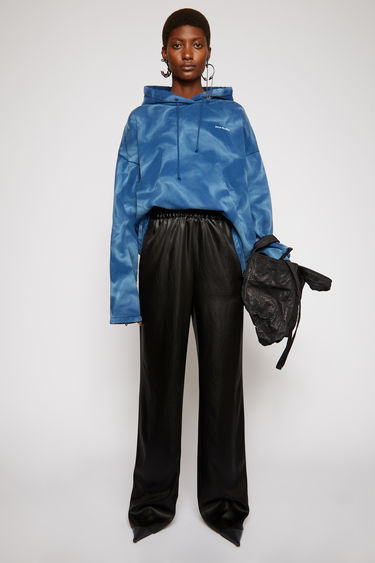 Acne Studios black satin trousers are tailored in a straight-leg shape that drapes loosely over the leg and finished with an elasticated waistband with drawstrings on the side.