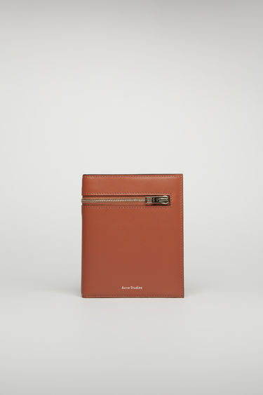 Acne Studios almond brown trifold wallet is crafted with five card slots, three receipt partitions and two zipped pockets from grained leather and accented with a silver-tone metal zip across the front.