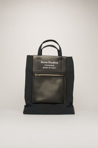 Acne Studios Baker Out M black/black is a medium-sized tote bag with an embossed logo pocket placed outside of the bag.