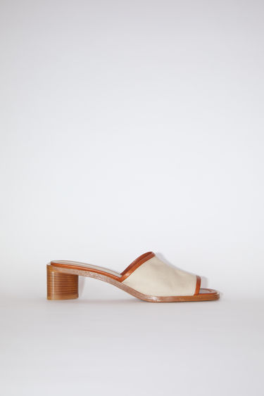 Acne Studios ecru/beige slip-on sandals are made of leather-trimmed canvas with open toes and block heels.