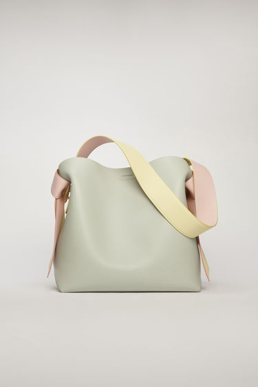 Acne Studios Musubi Midi pastel blue/pale pink bag features twisted knots inspired by the formation of traditional Japanese obi sash. It's crafted from soft grain leather and has a central zipped divider to store small essentials.