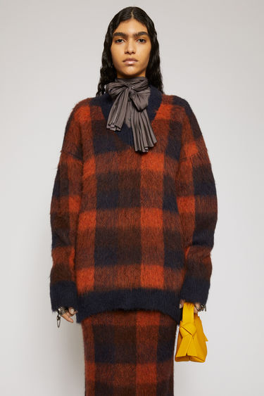 Acne Studios navy/orange sweater is knitted with an alpaca-blend yarn that has been brushed to enhance the fluffy texture. It's crafted to an oversized silhouette with a deep v-neckline and features a check jacquard pattern.