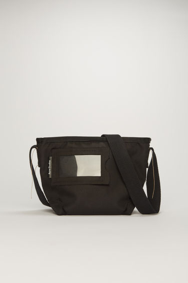 Acne Studios black crossbody bag is crafted to a structured rectangular shape with a transparent card pocket on front and features an adjustable shoulder strap.