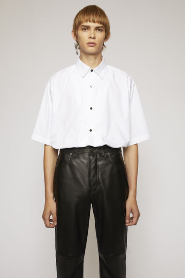 Acne Studios optic white shirt is crafted to a boxy silhouette from cotton poplin and features a pointed collar and mismatched buttons.