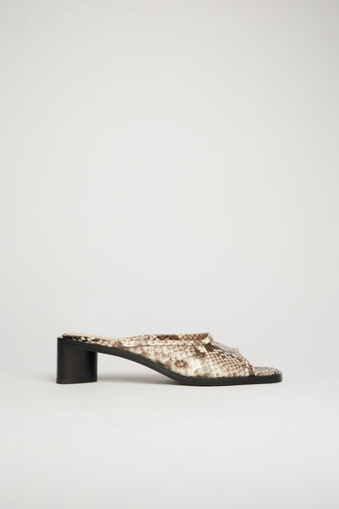 Acne Studios beige/black open-toe mules are crafted from python-print leather with a wide strap across the front, then set on a triangular block heel.