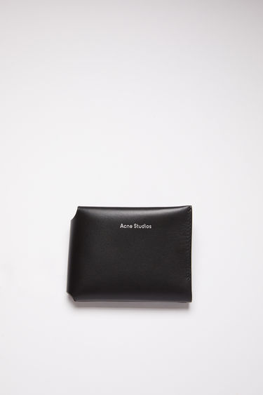 Acne Studios black trifold card wallet is made of soft grained leather with a coin pocket, bill sleeve, and four card slots, featuring a silver stamped logo on the front.