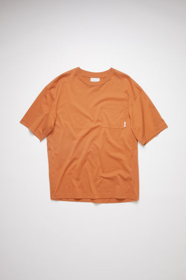 Acne Studios cognac brown crew neck t-shirt is made of cotton, featuring a single chest pocket with an Acne Studios logo tab.