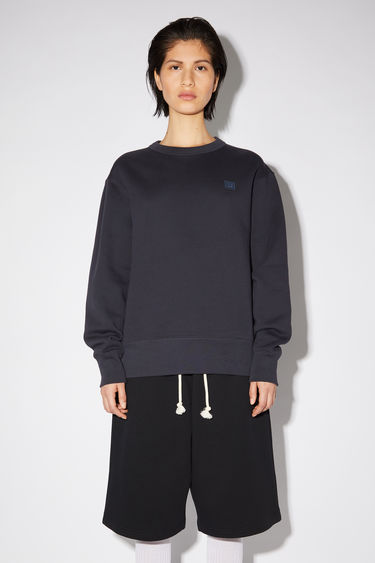 Acne Studios navy crew neck sweatshirt is made of organic cotton with a face patch and ribbed details.