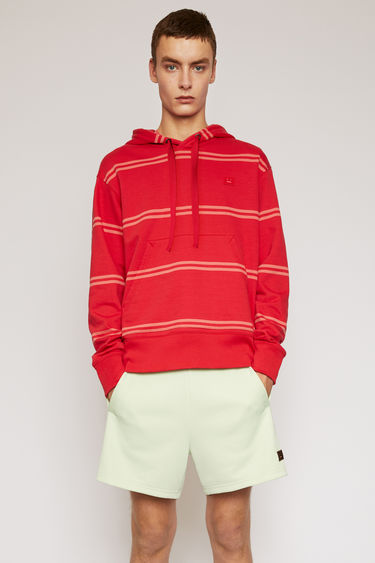 Acne Studios poppy red hooded sweatshirt is patterned with spaced stripes and finished with a tonal face-embroidered patch on the chest.