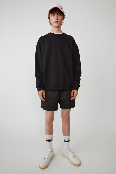 Acne Studios black sweatshirt is crafted from midweight loopback jersey to an oversized silhouette with dropped shoulders and accented with a tonal face-embroidered patch on the chest.